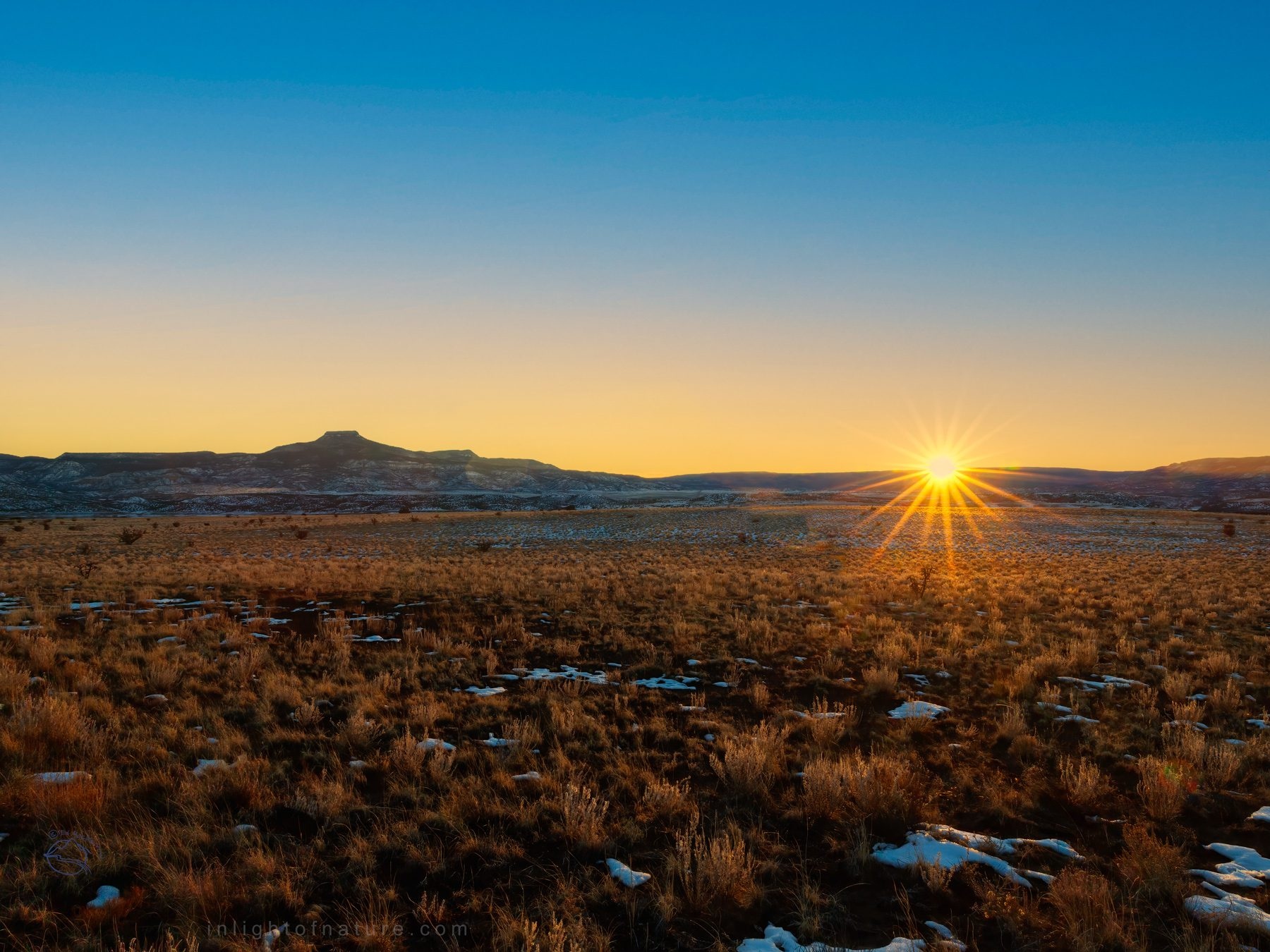 Sun setting on the horizon on Winter Solstice 2020 by Cerro Pedernal, New Mexico